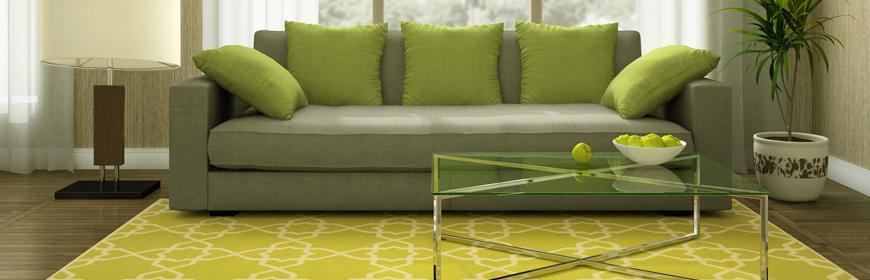 Fotografi på en soffa med kuddar och soffbord av glas samt en golvlampa