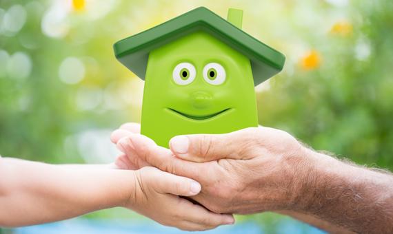Grönt leksakshus i kupade händer