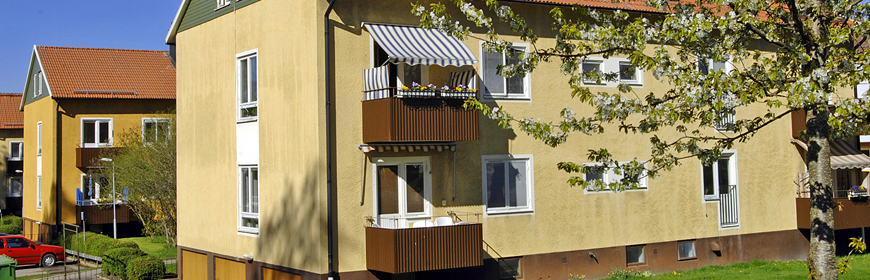 Gula tvåvåningshus med rött tegeltag och bruna balkonger