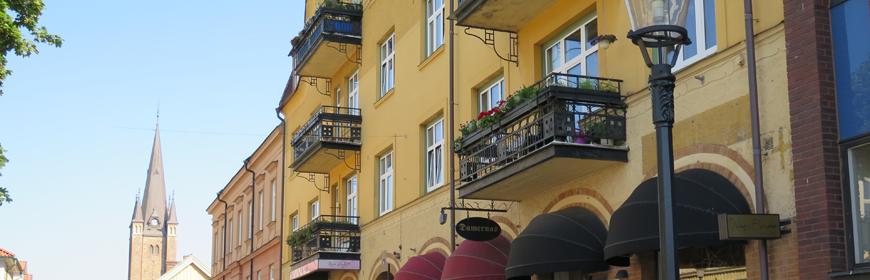Gult flervåningshus med svarta balkonger