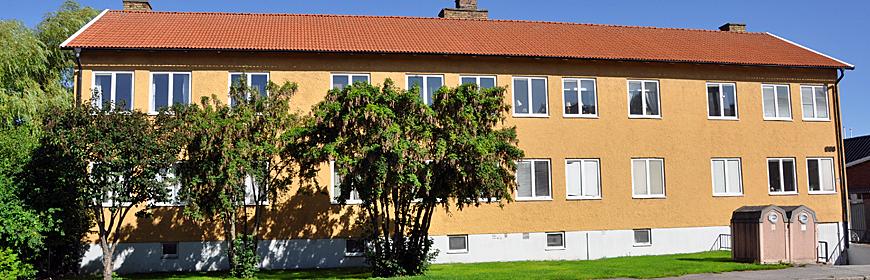 Gult tvåvåningshus med träd framför