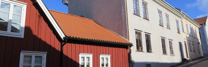 Ett grått och ett cremefärgat tvåvåningshus i gamla stan samt ett rött trähus
