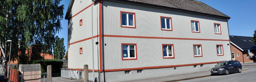 Grått tvåvåningshus med röda knutar