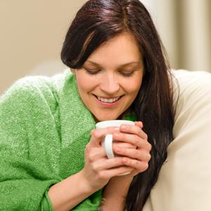 Frysande kvinna insvept i en filt och håller en kaffekopp i händerna