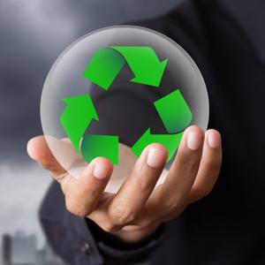 Hand som håller ett glasklot med återvinningssymbol