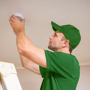 Man i grön keps och grön t-shirt som trycker på en brandvarnare