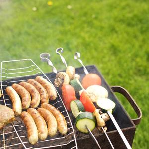Grillspett och grillkorv på tänd grill
