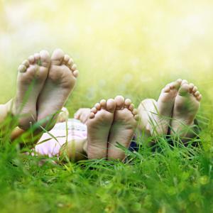 Tre par barfota fötter i gräset