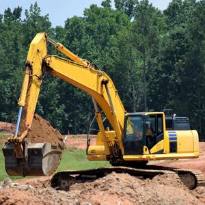 Gul grävskopa som gräver i marken